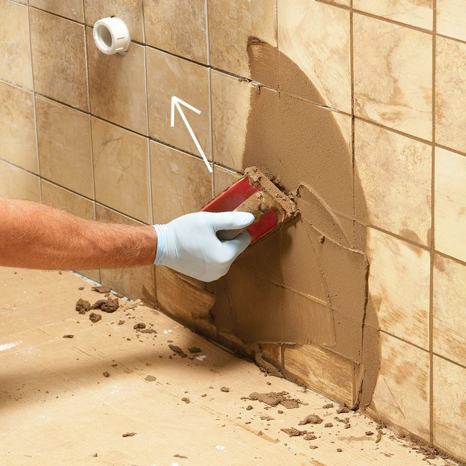 Spreading the grout along a wall of tile | Construction Pro Tips