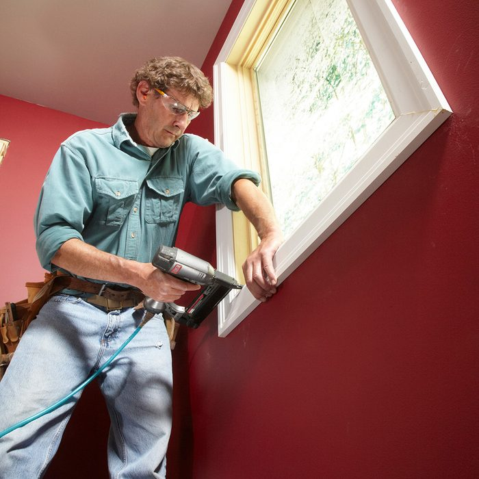 Man installing trim around a window   Construction Pro Tips