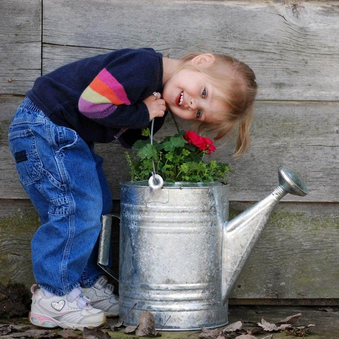 little girl repurposed watering can flower pot