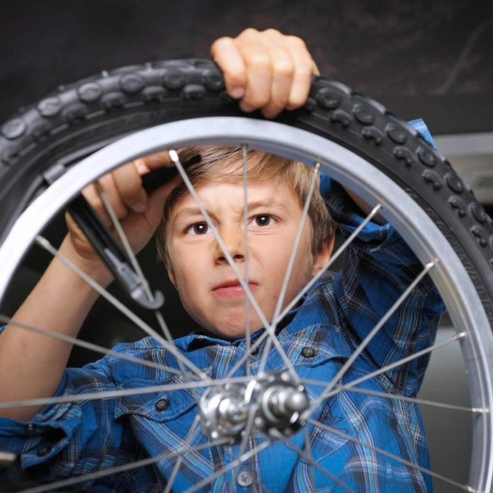 boy fixing bike tire