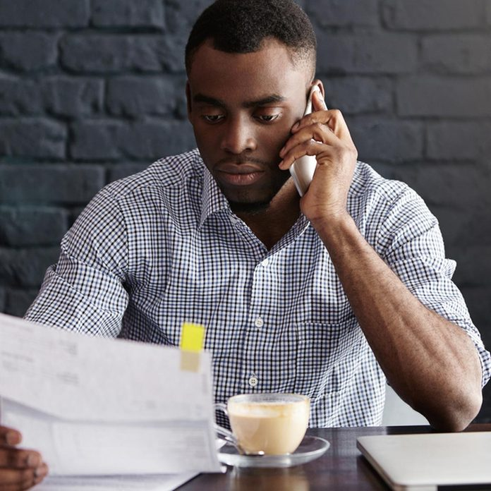 man researching business contact references on the phone