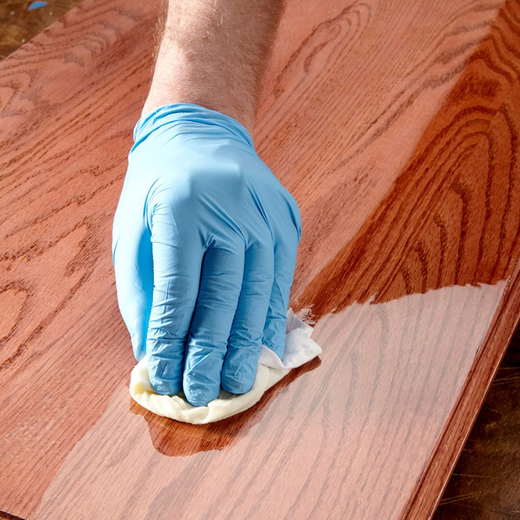 Wiping poly finish on wood with a rag | Construction Pro Tips