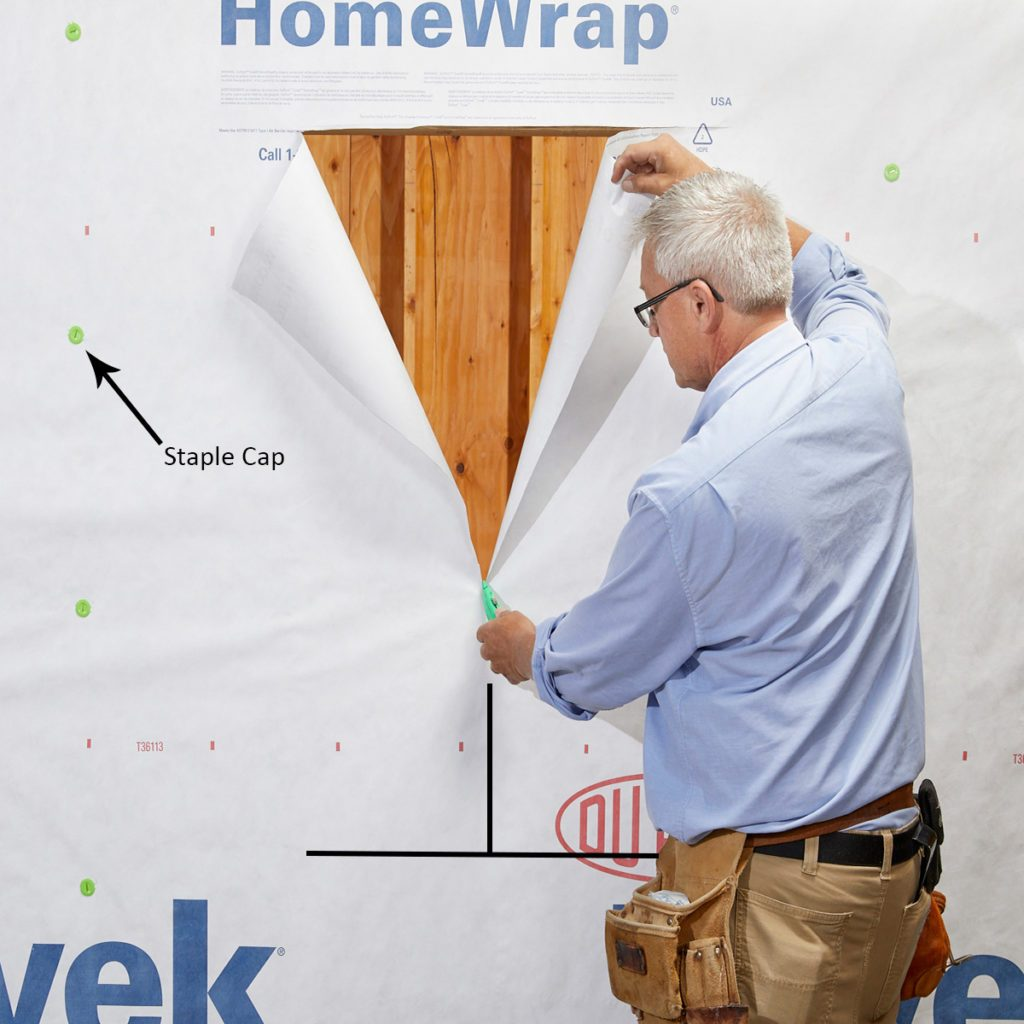 Man cutting a hole in the Tyvek   Construction Pro Tips