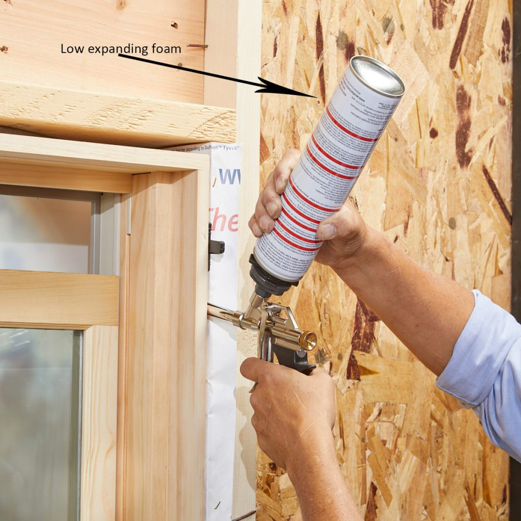 Using low-expanding foam to foam up the sides of a window   Construction Pro Tips