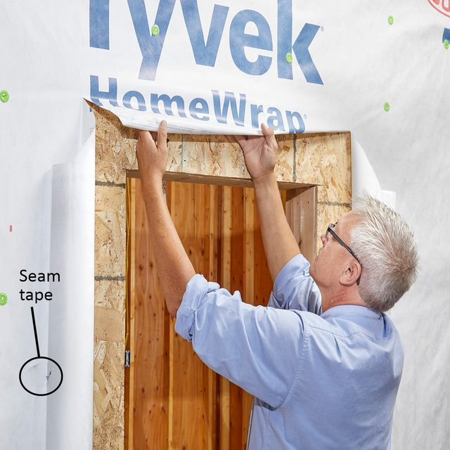 Man rolling Tyvek up and under | Construction Pro Tips