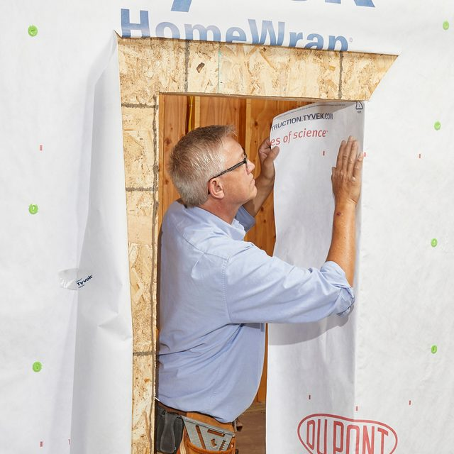 Man folding in the sides of the Tyvek | Construction Pro Tips
