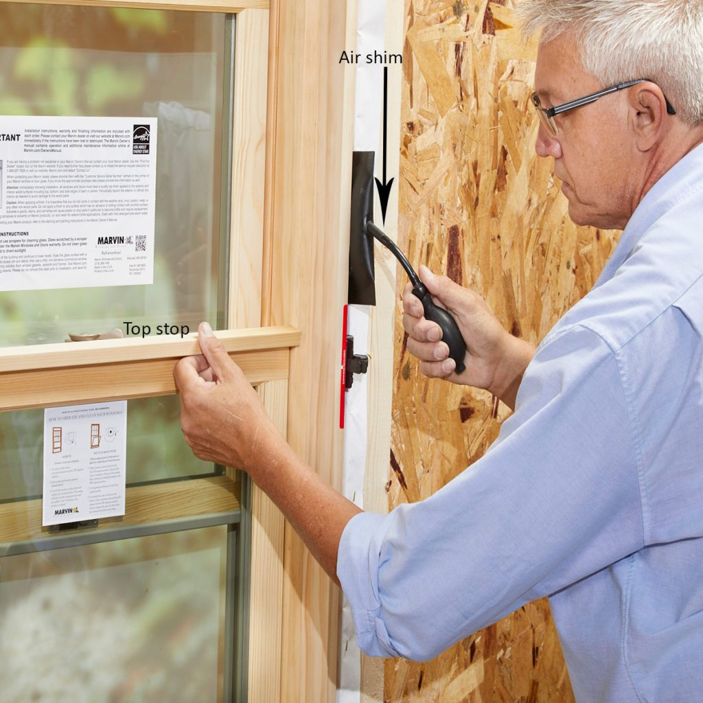 Man using an air shim to install a window   Construction Pro Tips