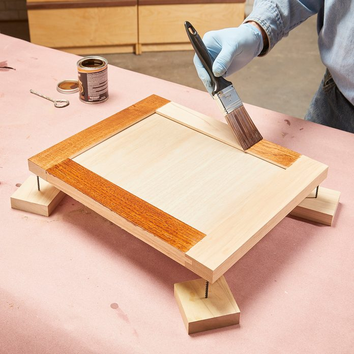 Brushing stain onto cabinet door frame   Construction Pro Tips