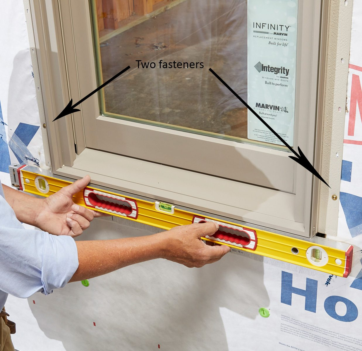 Man leveling and fastening the bottom of a window   Construction Pro Tips