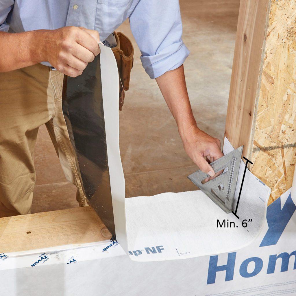 Man installing window pan flashing on window sill   Construction Pro Tips