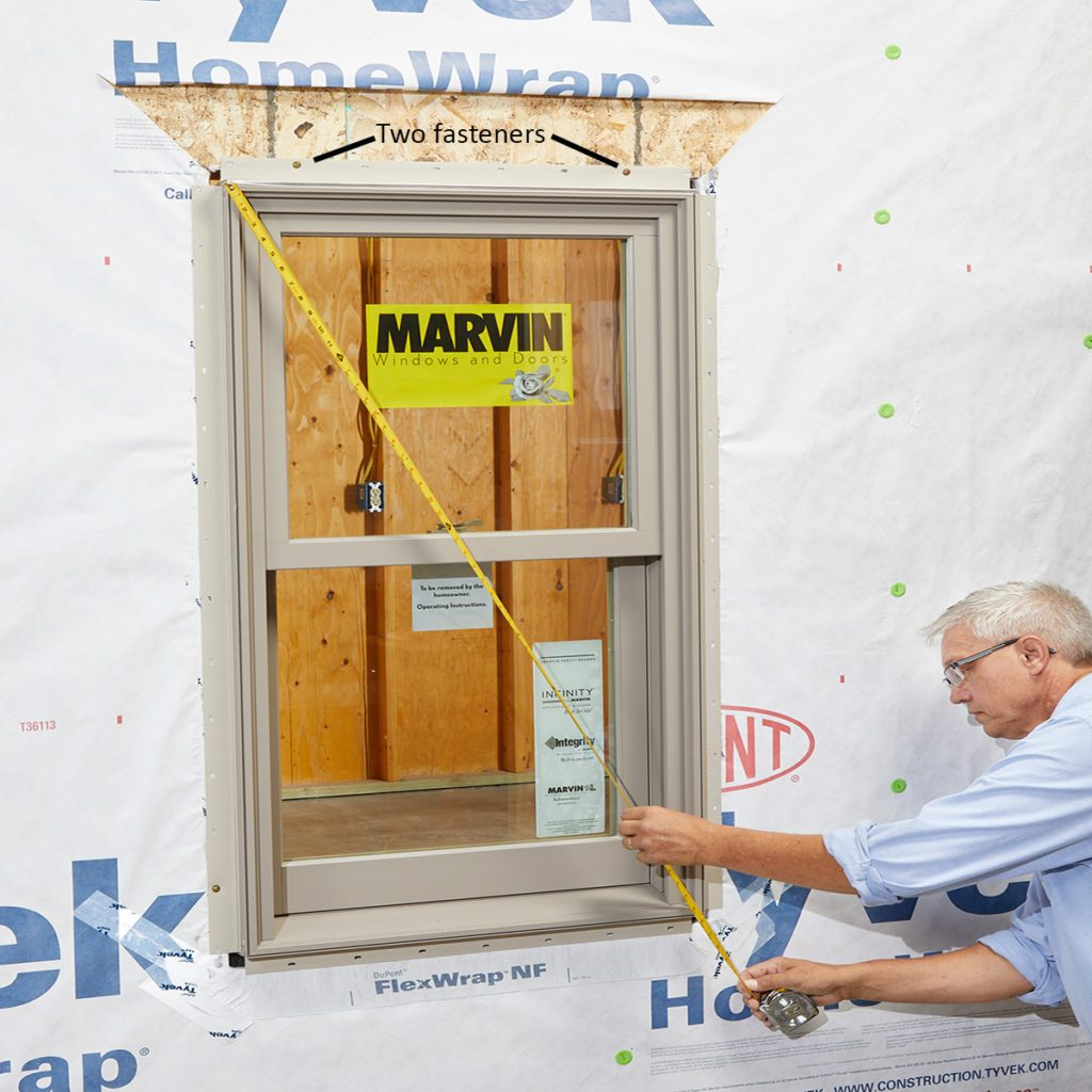 Man squaring and fastening the window with a measuring tape   Construction Pro Tips