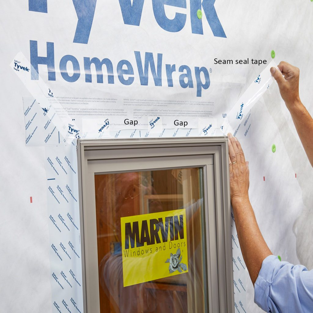 Taping the top flaps of Tyvek down after window installation   Construction Pro Tips