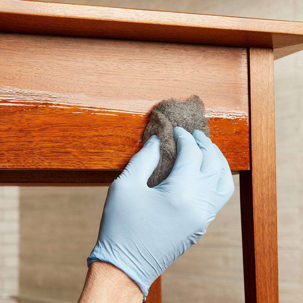 Wiping final coat of poly onto wood project with steel wool | Construction Pro Tips