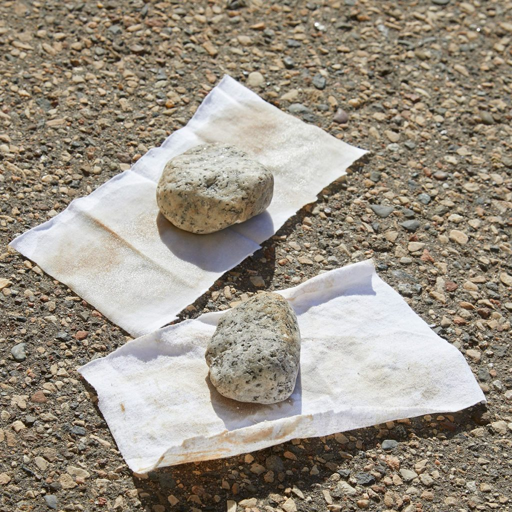 Rocks weighing down two oily rags on ground | Construction Pro Tips