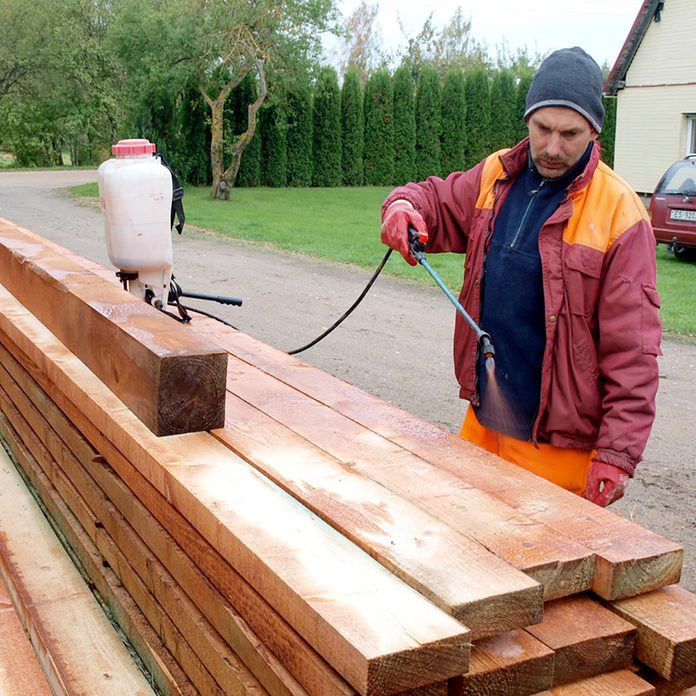 Man spraying treatment onto lumber | Construction Pro Tips