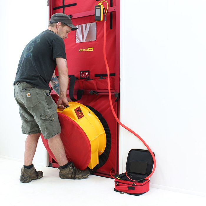 Putting a fan in place for a blower door test   Construction Pro Tips