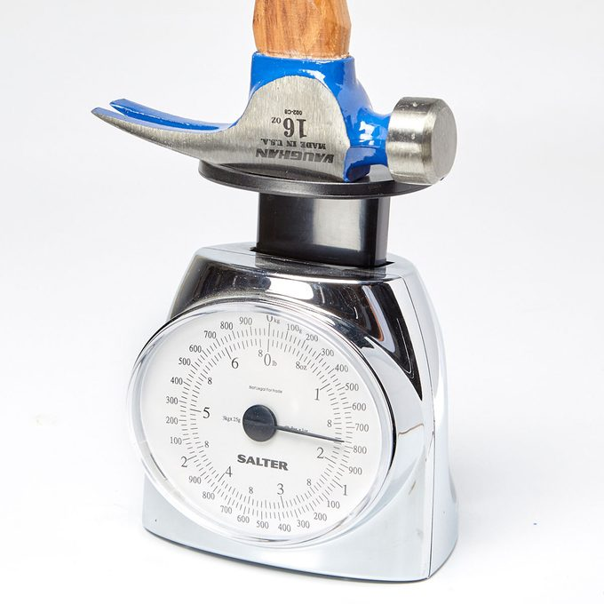 Hammer head being weighed on a scale | Construction Pro Tips