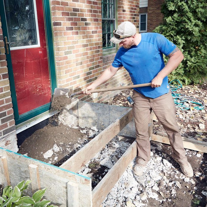 Man adding fill inside the forms for concrete steps   Construction Pro Tips