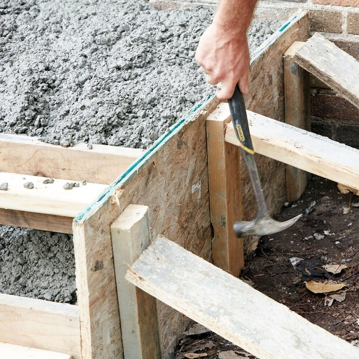 Tapping on the sides of the forms to get concrete to settle   Construction Pro Tips