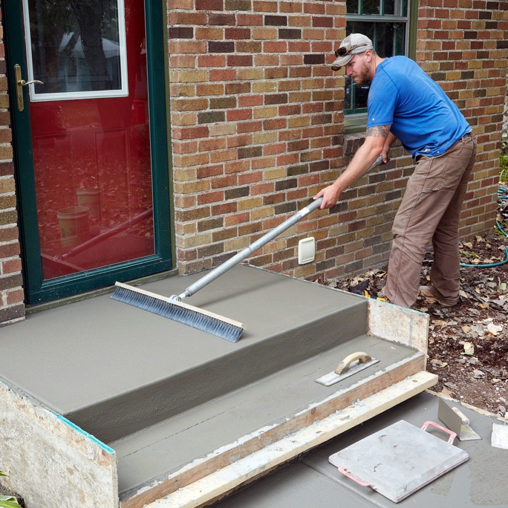 Brooming the top of the sidewalk for a nice finish | Construction Pro Tips