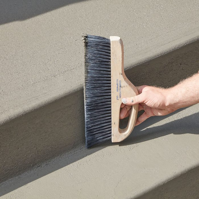 Brooming the edges of the step   Construction Pro Tips