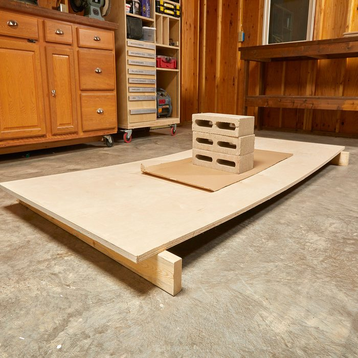 Removing the bow from plywood with cinderblocks   Construction Pro Tips