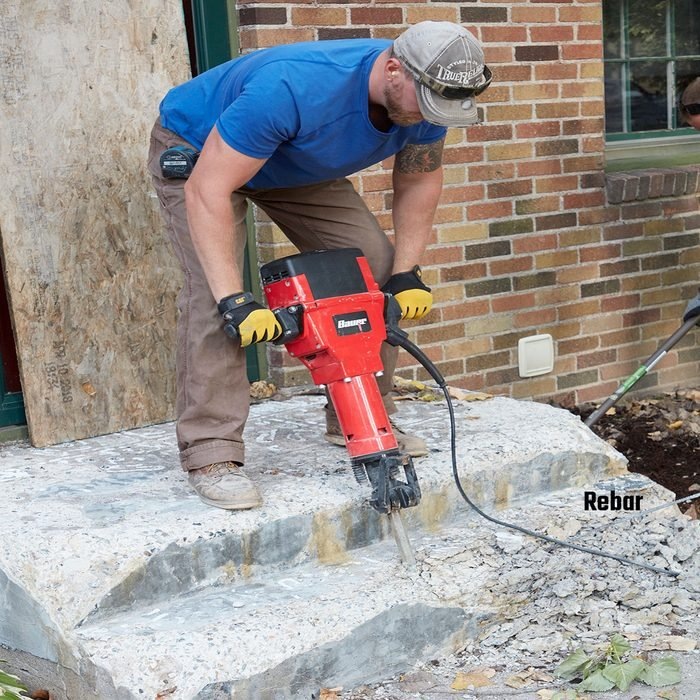 Breaking down an old step with a jackhammer   Construction Pro Tips