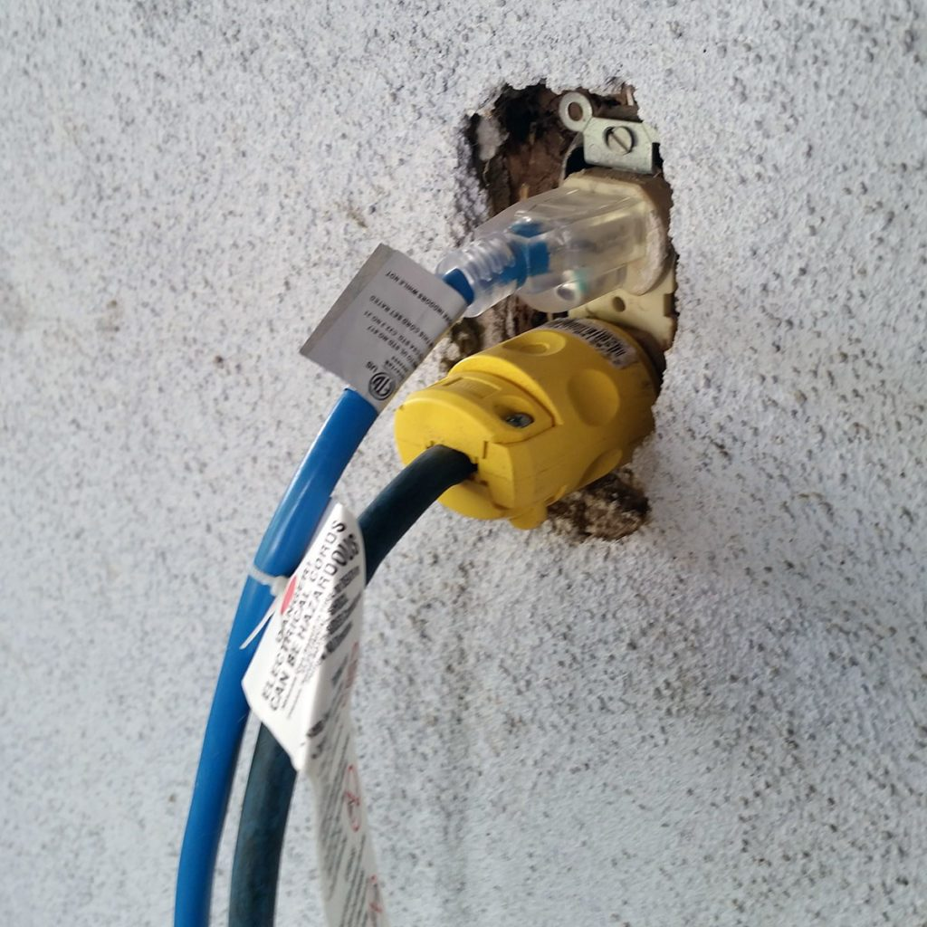Two cords plugged into a shabby exterior outlet | Construction Pro Tip