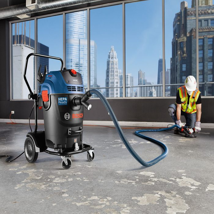 Man vacuuming floors with a Bosch vacuum | Construction Pro Tips