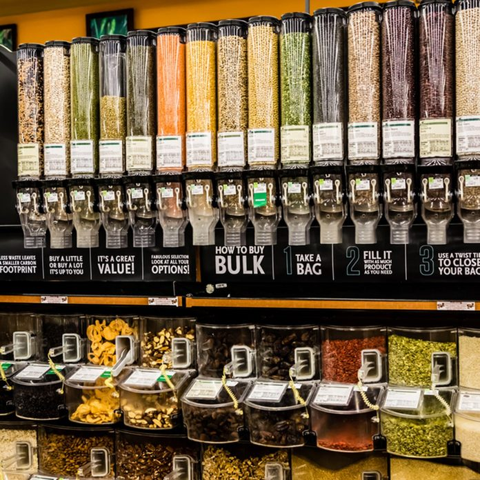 A large selection of bulk dry foods in clever dispensers and a weighing scale at an upscale grocery store