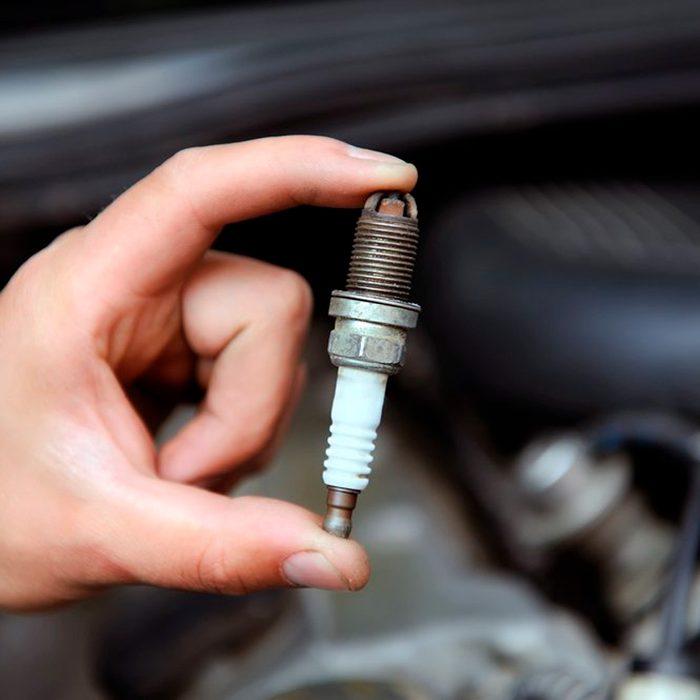 man holding a spark plug