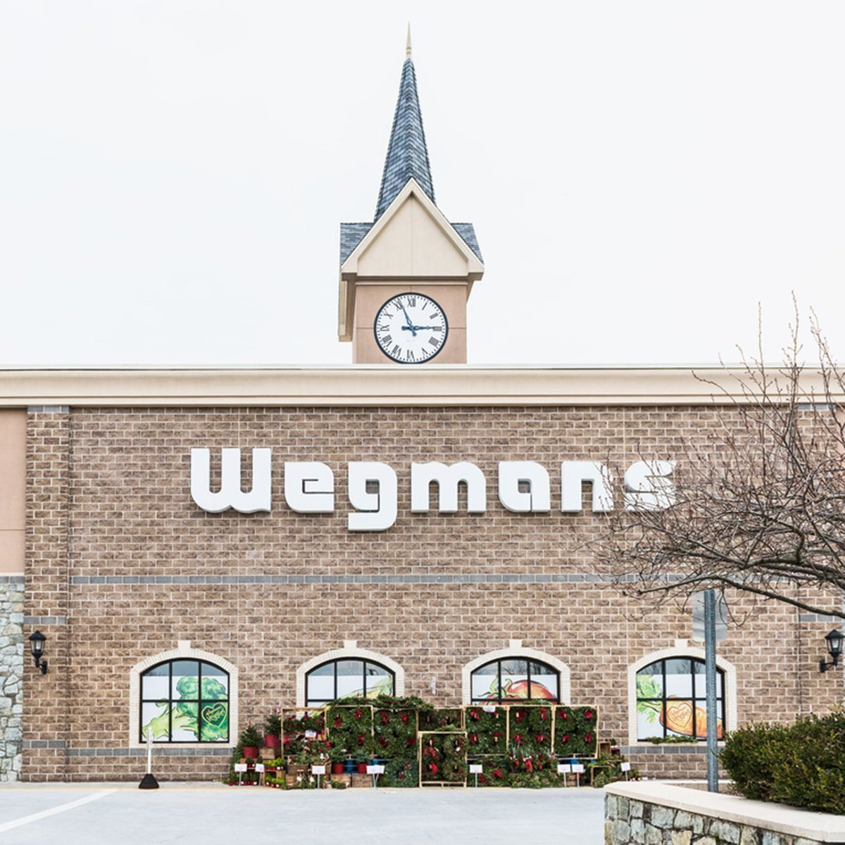 Wegmans grocery store facade and sign with people and Christmas wreath decorations