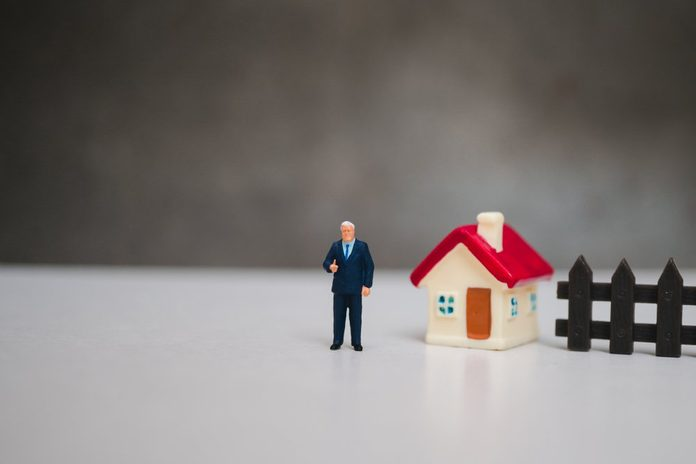 Miniature people, businessman standing with mini house using as business and family concept