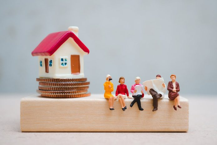 Miniature people sitting on wooden block with mini house on stack coins using as business, finance and social concept