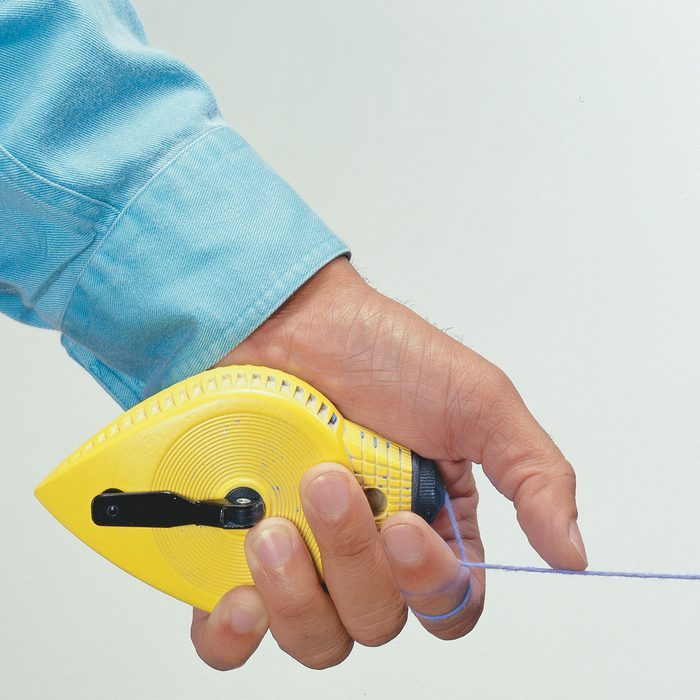 Hand holding a chalkline with a thumb on the string | Construction Pro Tips
