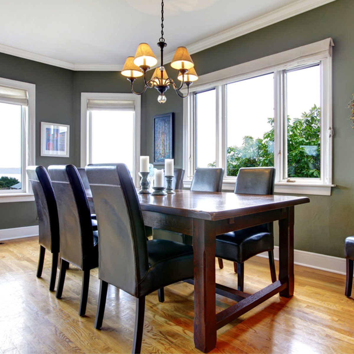 Large green dining room with leather chairs and large windows.