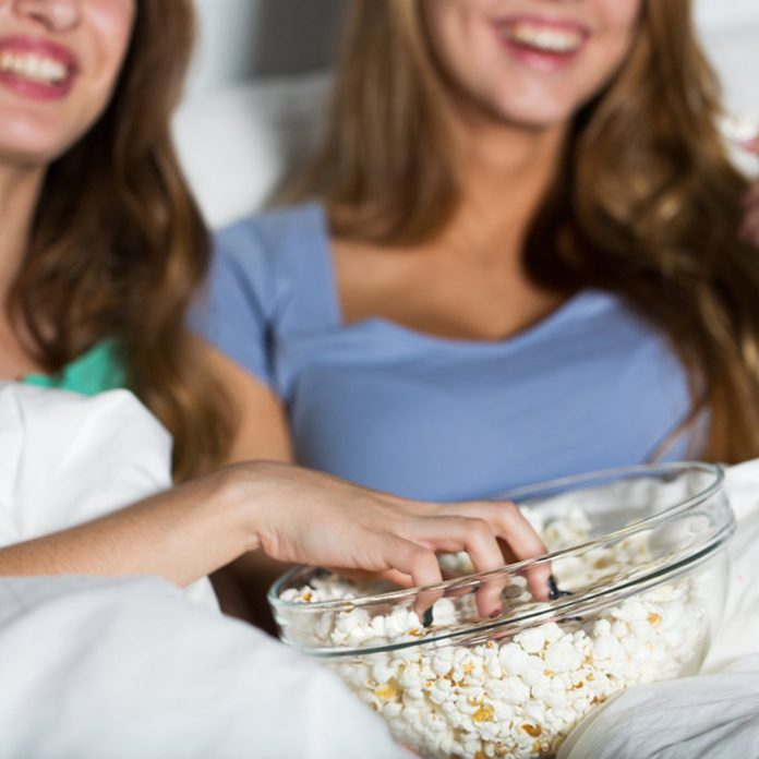 close up of happy friends or teenage girls eating popcorn and watching movie