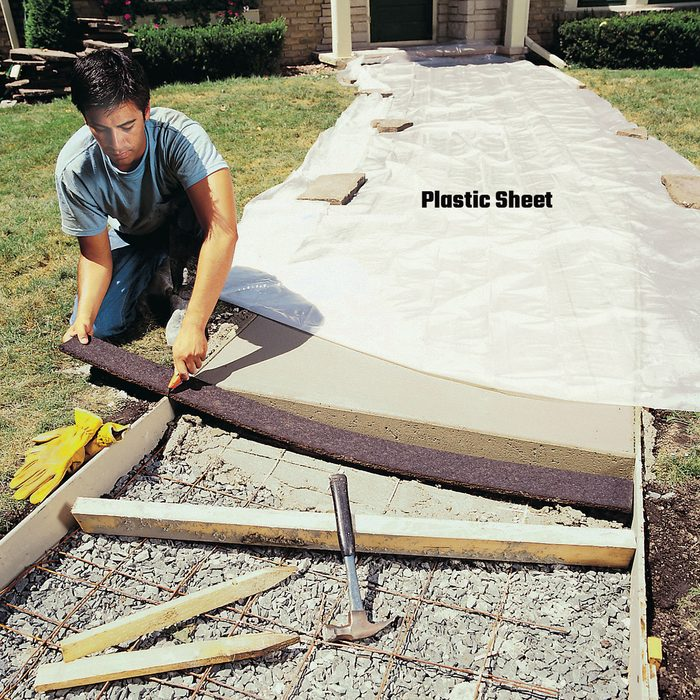 Man laying plastic sheets over concrete | Construction Pro Tips