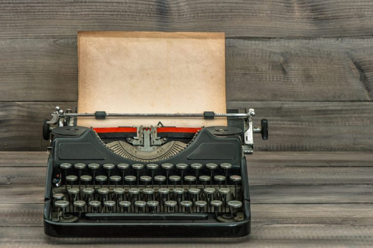 antique typewriter with grungy textured paper page on wooden table. vintage style still life