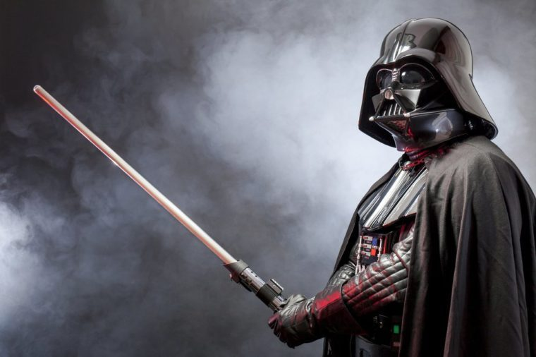 SAN BENEDETTO DEL TRONTO, ITALY. MAY 16, 2015. Portrait of Darth Vader costume replica with his sword . Lord Fener is a fictional character of Star Wars saga. Black background with smoke