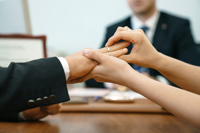 A woman puts a wedding ring in a registry office for a man. Marriage and hands close-up against the background of the ceremony master.