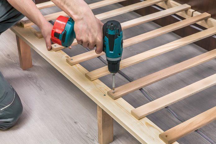 Wooden furniture assembling- woodworker screwing screws using a cordless