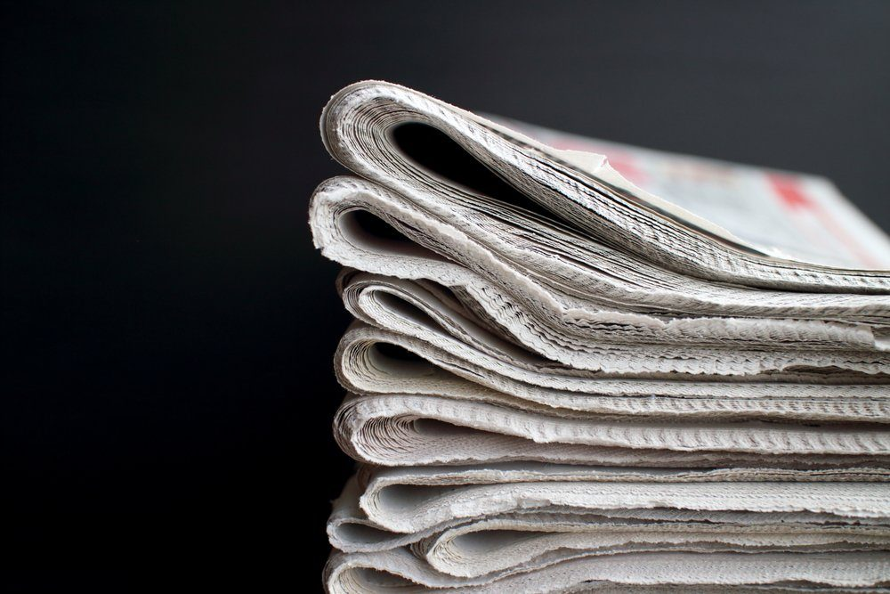 Stack of folded newspapers in front of a black background with copy space