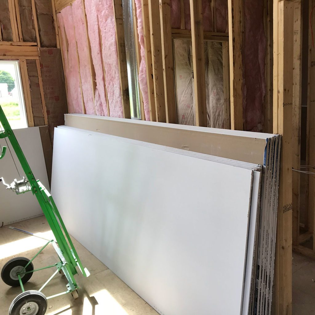 Drywall stacked against bare framing   Construction Pro Tips