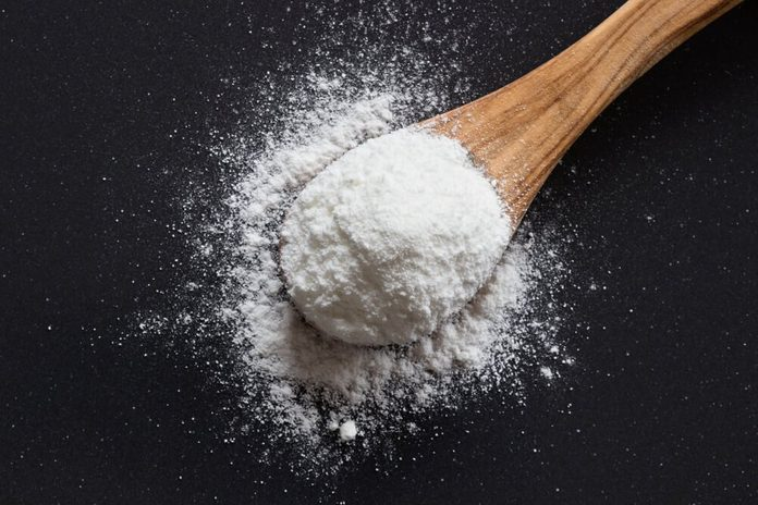 Baking soda on a wooden spoon on dark background, top view, sodium bicarbonate, powder, natural, cooking, baking,