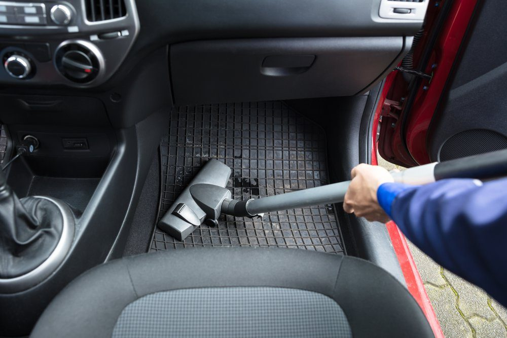 Close-up Of Handyman's Hand Vacuuming Car Mat With Vacuum Cleaner