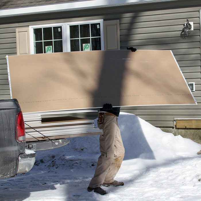 Person carrying lightweight drywall   Construction Pro Tips