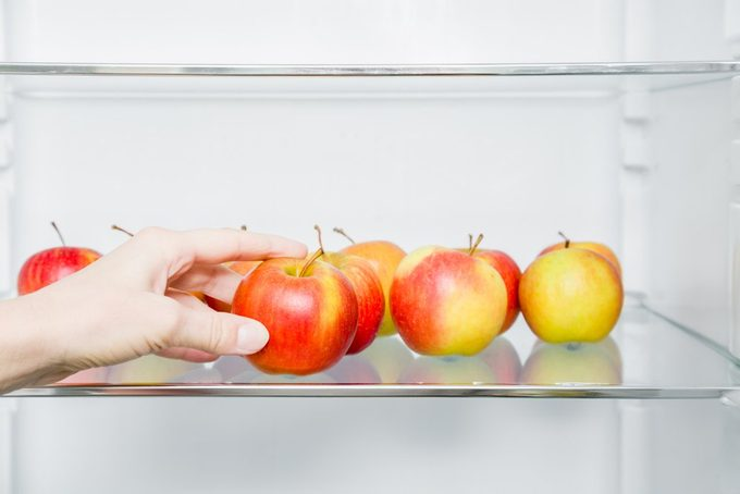 Woman's hand taking beautiful, fresh, colorful apple from fridge shelf in the kitchen. Healthy sweet food concept. New start for healthy nutrition, body slimming, weight loss. Cares about body.