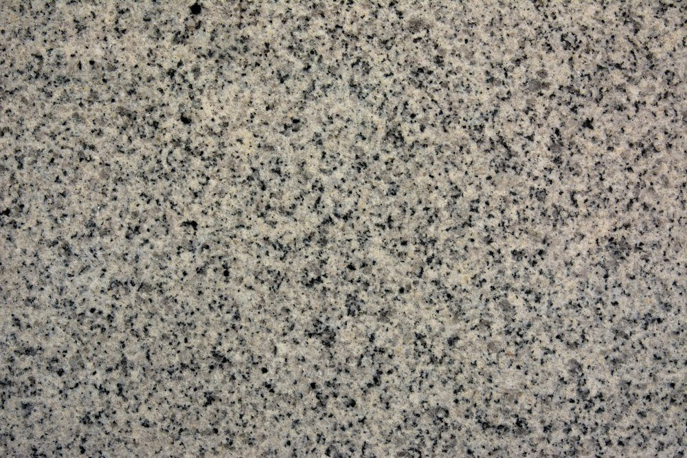 Polished granite texture with pink hues and black