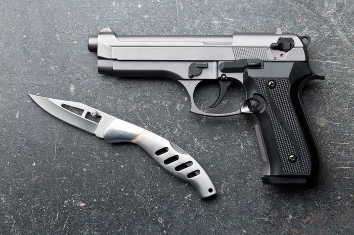 handgun and knife on old background
